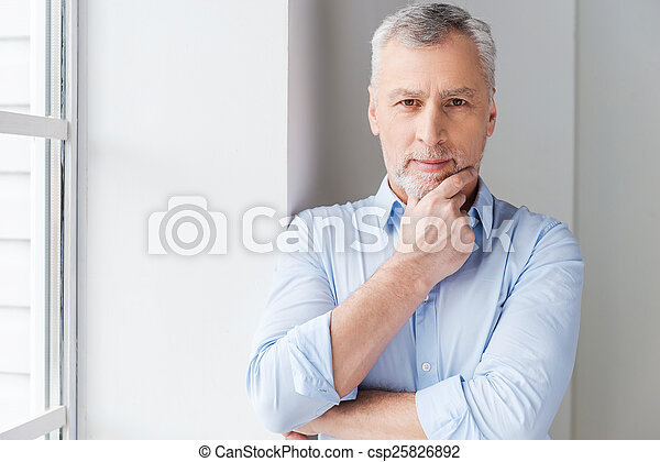 Thinking about solutions. Thoughtful grey hair senior man in shirt looking away while standing near the window