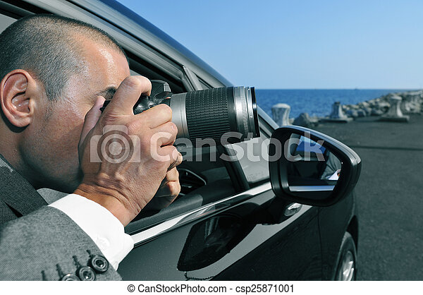detective or paparazzi taking photos from inside a car - csp25871001
