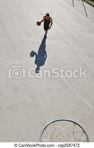 gorup of young boys who playing basketball outdoor on street with long shadows and bird view perspective