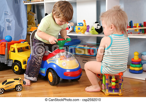 two children in playroom  with toy scooter - csp2592010