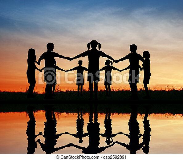 silhouette children. sunset pond. - csp2592891