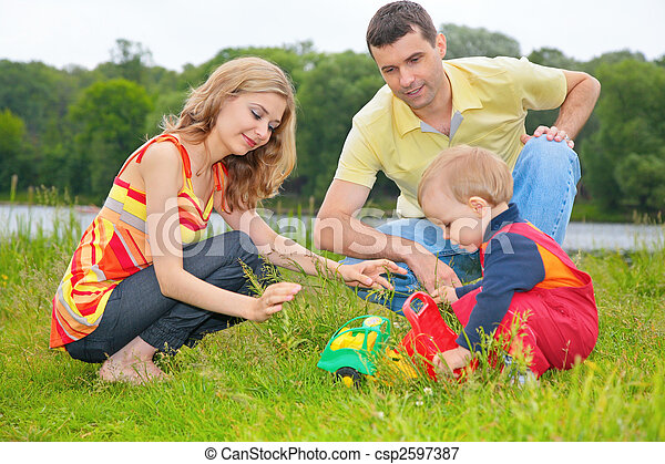 child sits on grass with parents and plays with toy - csp2597387
