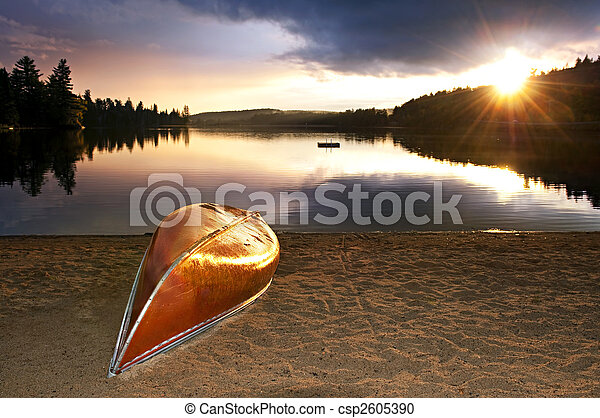 Lake sunset with canoe on beach - csp2605390
