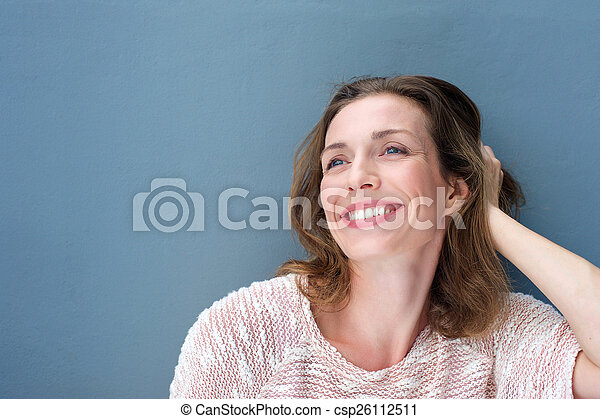 Happy older woman laughing with hand in hair