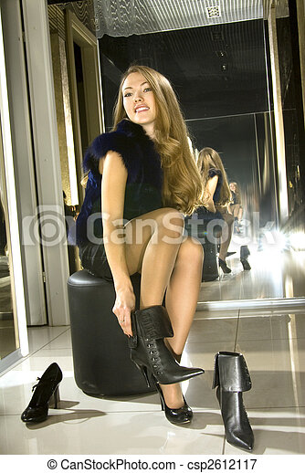 girl fits on a boots in a boutique - csp2612117