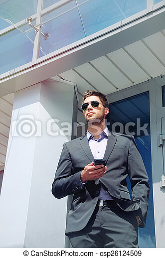attractive young businessman with phone device on office buildin