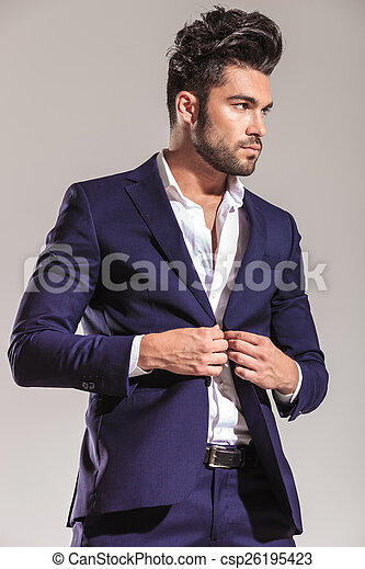 Handsome young business man closing his jacket.
