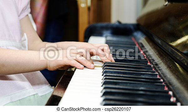 Girl\'s hands and piano keyboard close-up view