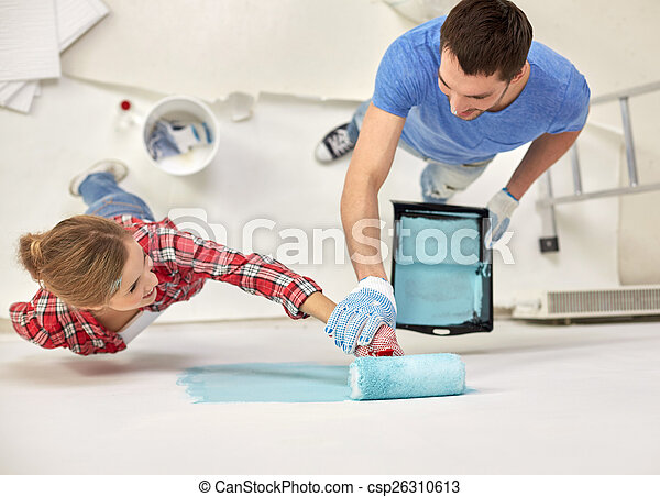 couple with paint roller painting wall at home