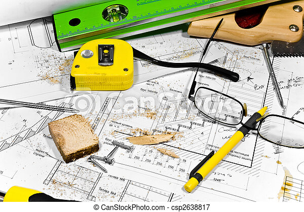 Busy hobby workbench. Different carpenter tools: saw, hummer, tape measure, level ruler, screwdriver are lying in the saw dust upon the blueprints and drawings along with screws, pencil and glasses. - csp2638817
