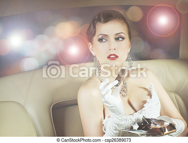 Young and beautiful celebrity woman sitting in a luxury car and eating a chocolate