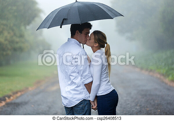 young couple in love under umbrella in the rain