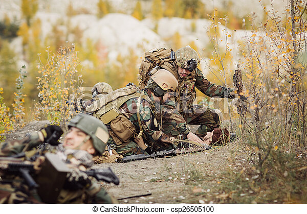 Soldiers team medic assists wounded taliban soldier