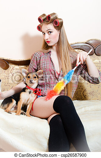 cleaning sexy service: beautiful little dog with red ribbon sitting with pinup girl in bed seriously looking at camera on white copy space background picture