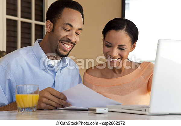 A happy African American man and woman couple in their thirties working on a laptop computer and looking at paperwork - csp2662372