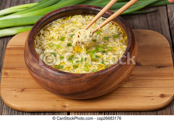 Chopsticks in bowl with traditional egg drop soup asian appetizer meal on wooden desk