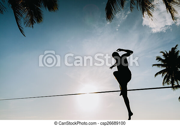 teenage jumping on slackline with sky view