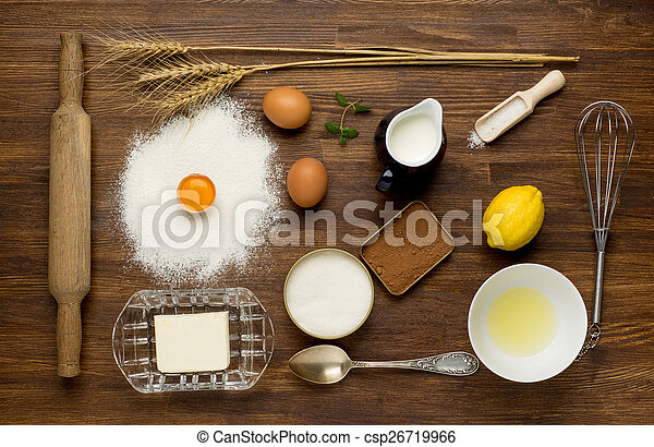 Baking cake in rural kitchen - dough recipe ingredients (eggs, flour, milk, butter, sugar) on vintage wooden table from above.