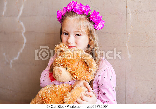 Close up portrait of adorable little girl with bright pink flower headband, holding teddy bear