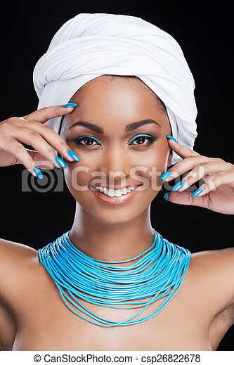 Bright emphasis. Beautiful African woman wearing white headscarf and smiling while looking at camera and standing against black background
