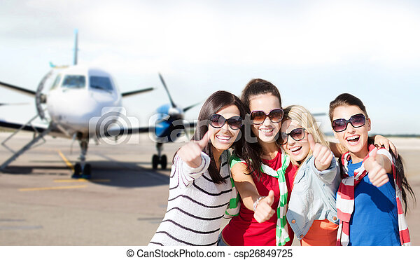 happy teenage girls showing thumbs up at airport