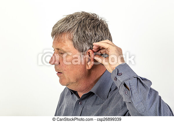 man puts hearing aid in the ear