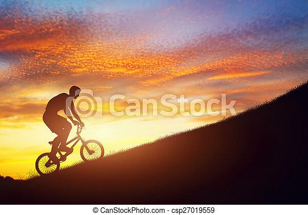 Man riding a bmx bike uphill against sunset sky. Strength, challenge. - csp27019559