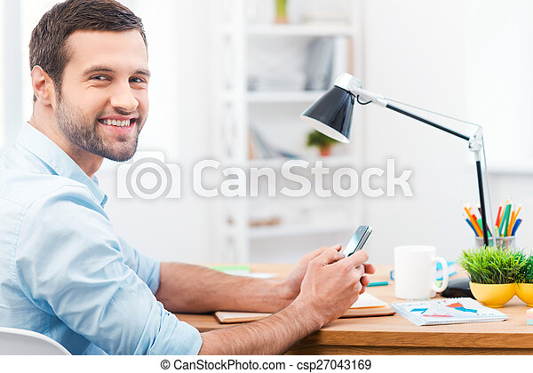 In love with my job. Side view of handsome young man in shirt holding mobile phone and smiling at camera while sitting at his working place