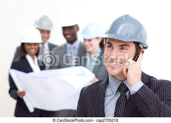 Confident male architect with his team in the background