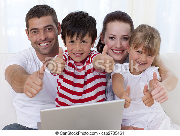 Family at home using a laptop with thumbs up - csp2705461