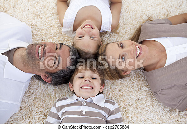 Family lying on floor with heads together - csp2705884