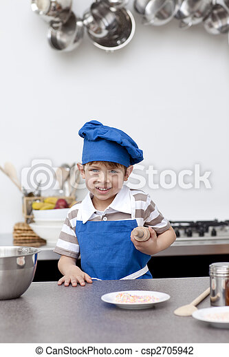 Little boy with blue hat and apron baking - csp2705942
