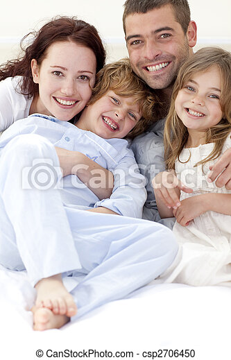 Portrait of young family lying in bed - csp2706450