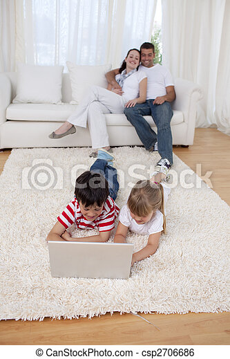 Brother and sister using a laptop on floor in living-room - csp2706686