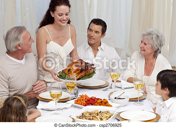 Woman showing turkey to her family for Christmas dinner - csp2706925
