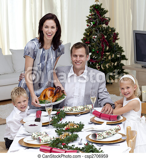 Parents and children celebrating Christmas dinner with turkey - csp2706959