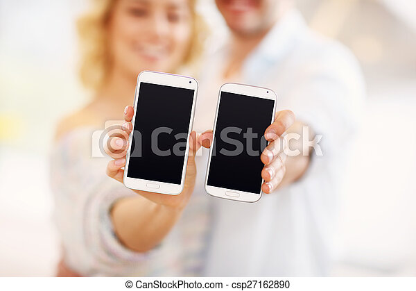 Couple showing their smartphones