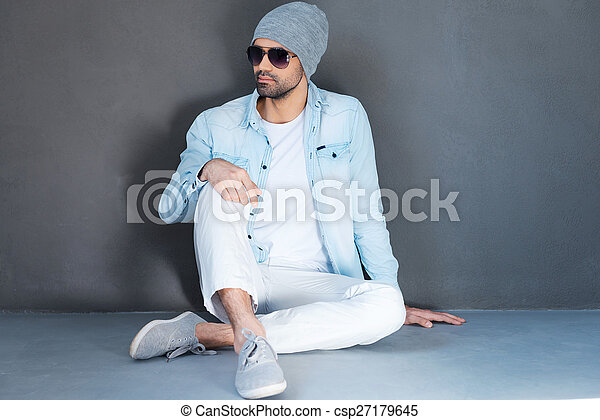 Relaxed and carefree. Handsome young man in eyewear sitting on the floor against grey background