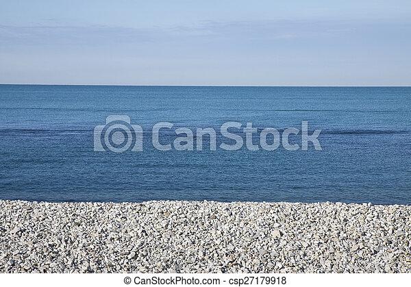 Calm sea with white stones on the beach
