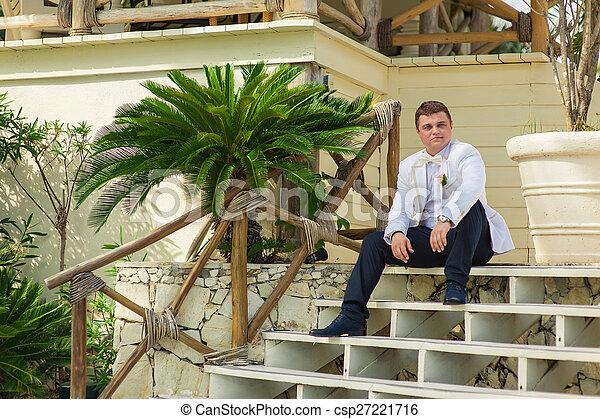 groom sitting on a palm tree on a tropical beach