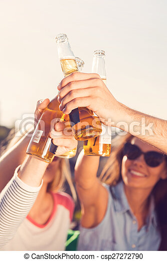 Beer time! Close-up of young cheerful people cheering with beer while sitting outdoors together
