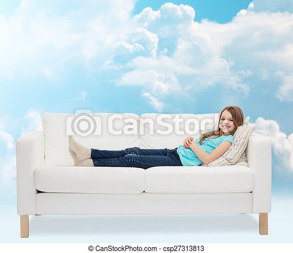 smiling little girl lying on sofa