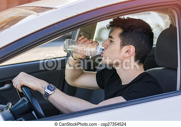 Young man driving car and drinking water from bottle