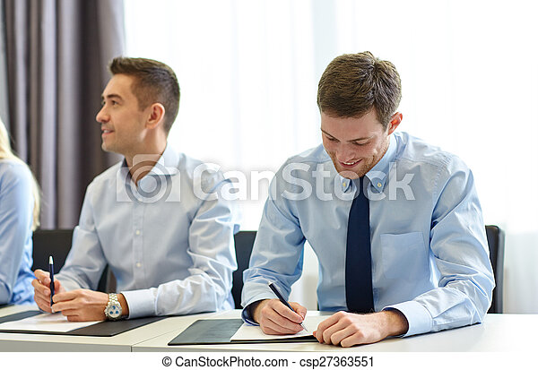 group of smiling businesspeople meeting in office