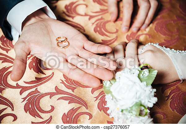 Wedding Couple\'s hands on the table and rings, bridal bouquet flowers