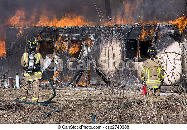 Firefighters standing in front of a burning house - csp2740388