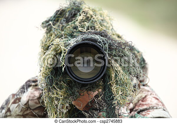 wildlife photographer using camouflage and pointing his huge 300mm 2.8 telephoto lens at you while outdoors - csp2745883