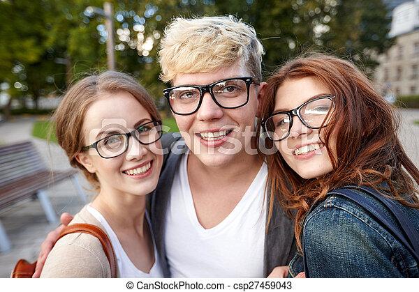 happy teenage students in eyeglasses at campus