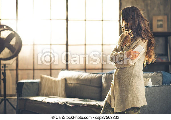Brunette looking away holding phone in a loft apartment