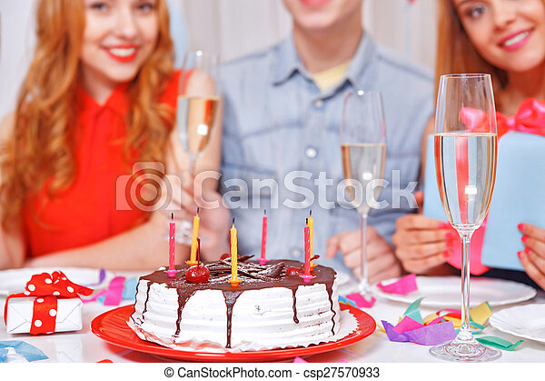 Young people celebrating a birthday sitting at the table - csp27570933